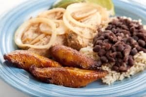 Closeup of Cuban dinner with focus on fried sweet plantains. Marinated roast pork with black beans and rice complete the meal.