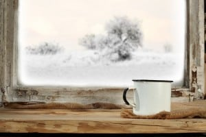 White mug on window sill looking out onto winter snow