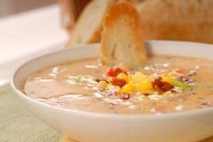 Bread being dipped in corn chowder.