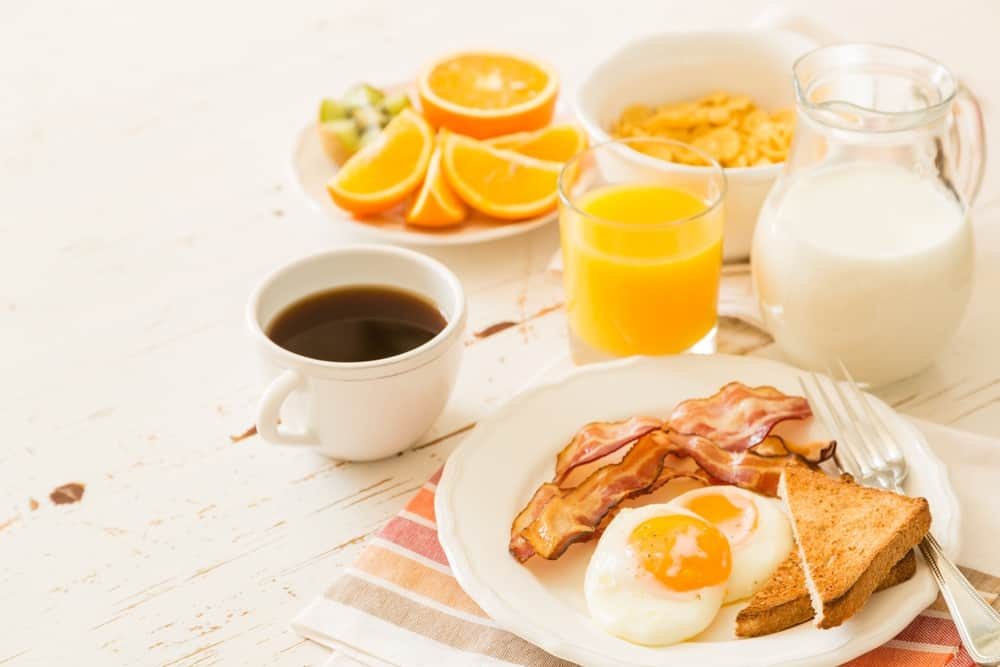 eggs, bacon, toast, milk, orange, and coffee